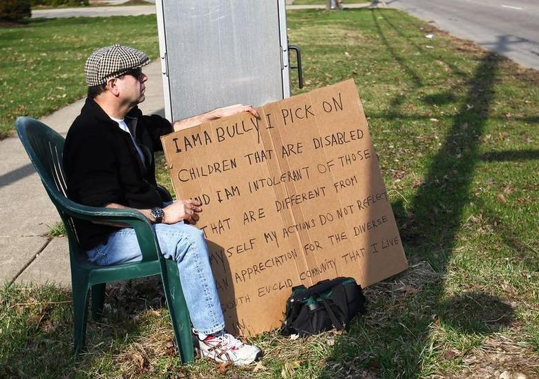 Edmond Aviv, 62, sits with a sign he made at a street corner in the Cleveland suburb of South Euclid, Ohio April 13, 2014. REUTERS/Aaron Josefczyk
