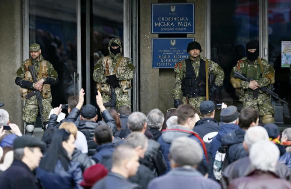 Pro-Russian armed men stand guard as pro-Russian supporters gather outside the mayor's office in Slaviansk April 14, 2014. REUTERS/Gleb Garanich