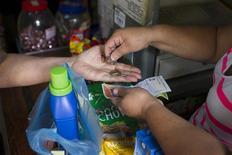 Un cliente recibe cambio tras pagar por unos artículos en un supermercado en Caracas, feb 14 2013. La oposición venezolana acusó al Gobierno de Nicolás Maduro de retrasar la publicación de la inflación del mes de marzo por razones políticas, argumentando que la tasa anual habría alcanzado un alarmante 60 por ciento. REUTERS/Carlos Garcia Rawlins