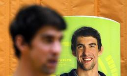 U.S. swimmer Michael Phelps stands next to a banner with his image during a promotional event in Sao Paulo December 4, 2013. REUTERS/Paulo Whitaker