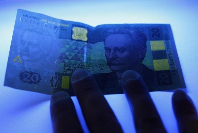 A cashier checks authenticity of an Ukrainian hryvnia banknote under ultraviolet (UV) light at a shop in Kiev February 21, 2010. REUTERS/Konstantin Chernichkin