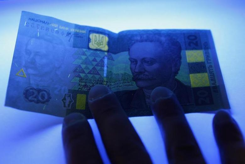 A cashier checks authenticity of an Ukrainian hryvnia banknote under ultraviolet (UV) light at a shop in Kiev February 21, 2010. REUTERS/Konstantin Chernichkin