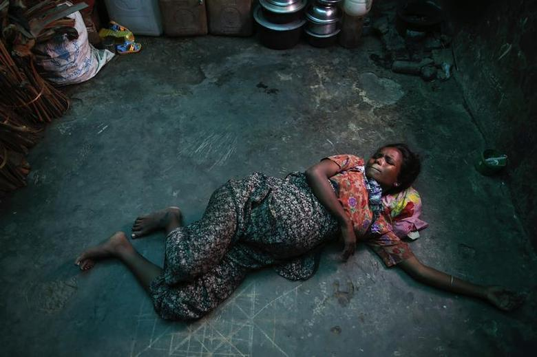 Roma Hattu, a Rohingya Muslim woman who is nine months pregnant and is displaced by violence, grimaces while experiencing labour pains on the bare floor of a former rubber factory now serving as her family's shelter near Sittwe April 28, 2013. REUTERS/Damir Sagolj