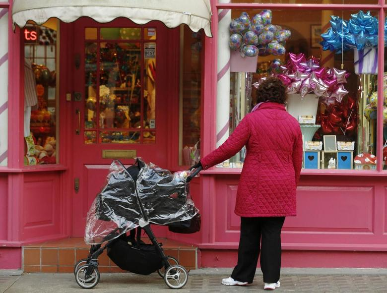 A woman stops to look in the window of a shop in London March 25, 2014. REUTERS/Luke MacGregor