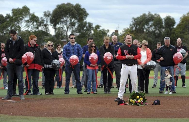 Peter Lane (2nd R), father of murdered Australian Christopher Lane, stands with other family members and Christopher's girlfriend Sarah Harper (C, not wearing glasses) during a memorial service held at Essendon Baseball Club in Melbourne August 25, 2013. REUTERS/Mal Fairclough
