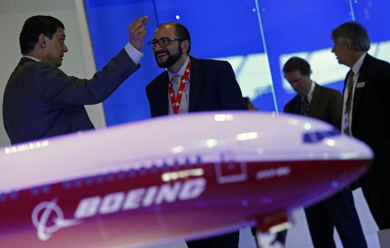 Visitors talk next to a Boeing 777X aircraft model at the Singapore Airshow February 13, 2014. REUTERS/Edgar Su