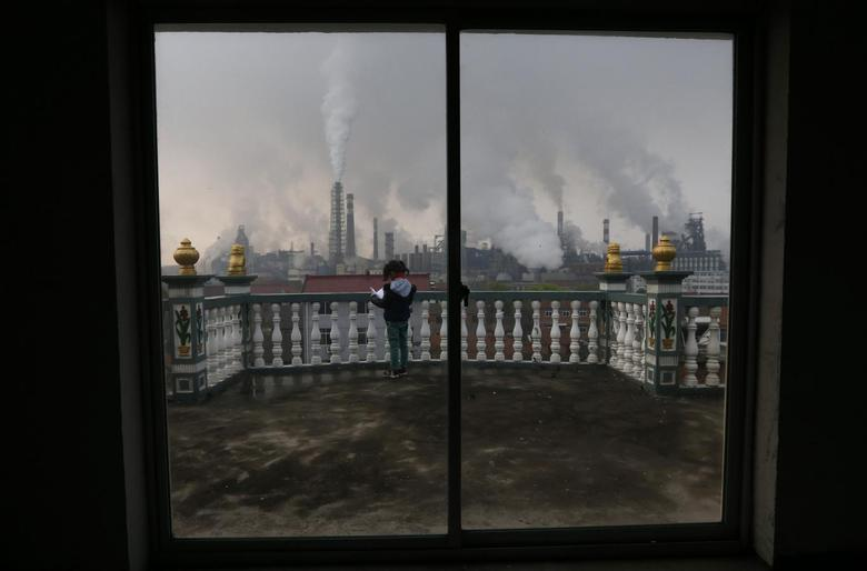 A girl reads a book on her balcony as smoke rises from chimneys of a steel plant, on a hazy day in Quzhou, Zhejiang province April 3, 2014.REUTERS/Stringer