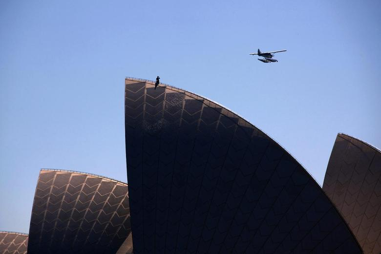 A worker watches a sea plane as it passes overhead as he stands atop of the Sydney Opera House on a sunny day November 14, 2013. REUTERS/David Gray