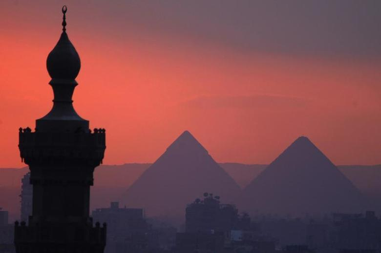 The sun sets on the minarets and the Great Pyramids of Giza (R) in Old Cairo December 31, 2013. REUTERS/Amr Abdallah Dalsh