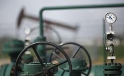 Вентили и датчики давления на фоне станка-качалки на месторождении нефти близ Гензерндорфе 8 апреля 2014 года. Цены на нефть снижаются накануне переговоров по украинскому вопросу между представителями Украины, России, США и ЕС, которые пройдут в четверг в Женеве. REUTERS/Leonhard Foeger