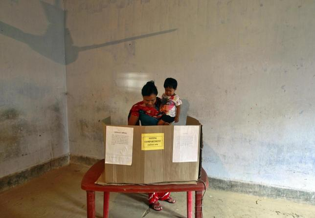 A woman holds her child while casts her vote at a polling station at Dhalai district in the northeastern Indian state of Tripura April 12, 2014. REUTERS/Jayanta Dey