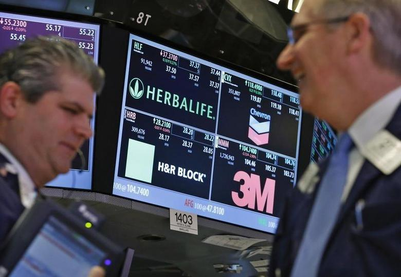 A screen displays the tickers symbols for; Herbalife, Chevron, H&R Block and 3M as traders work on the floor at the New York Stock Exchange, April 25, 2013. REUTERS/Brendan McDermid