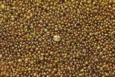 Oro granulado en la planta de la refinería Valcambi SA en Balerna, Suiza, dic 20 2012. El oro finalizaría el 2014 ligeramente por encima de los 1.250 dólares la onza debido a que una aceleración en el crecimiento económico de Estados Unidos y al fortalecimiento del dólar enfriarían el avance de los precios visto en el primer trimestre, mostró un sondeo de Reuters el martes. REUTERS/Michael Buholzer