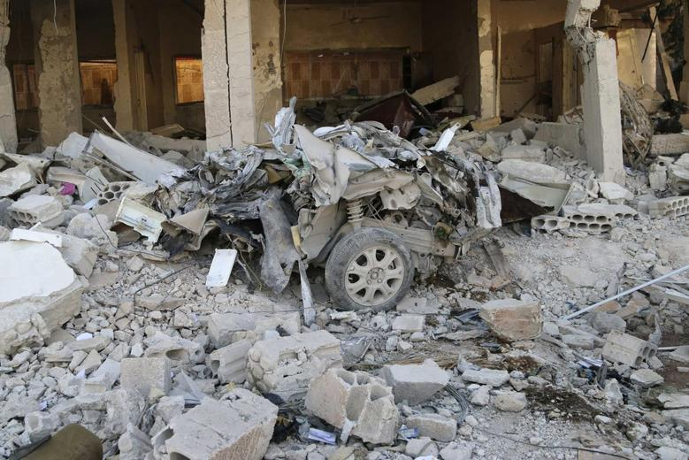 A wreckage of a car is seen amid damage at a site hit by what activists say was a barrel bomb dropped by forces loyal to Syria's President Bashar al-Assad in Kaheel village in the eastern countryside of Deraa April 14, 2014. Picture taken April 14, 2014. REUTERS/Mohamed Fares