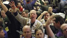 Traders in the corn options pit at the CME Group signal orders shortly before the closing bell in Chicago, in this February 11, 2011 file photograph. REUTERS/Frank Polich/Files