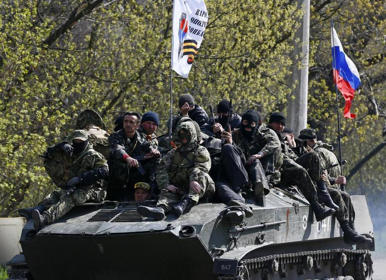 Armed men, wearing black and orange ribbons of St. George - a symbol widely associated with pro-Russian protests in Ukraine, drive an armoured personnel carrier, with a Russian flag seen on the top, in Slaviansk April 16, 2014. REUTERS/Gleb Garanich