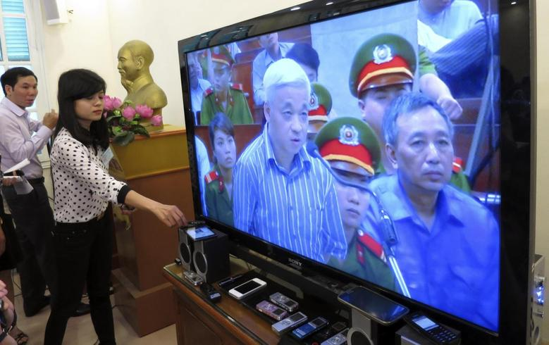 A journalist places a recording device next to a TV screen showing live images from a courtroom where Vietnamese tycoon and former banker Nguyen Duc Kien speaks during his trial in Hanoi April 16, 2014. REUTERS/Nguyen Phuong Linh