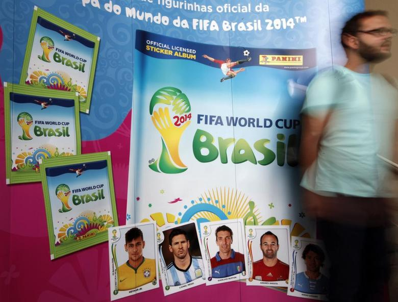 A man walks past the banner of the official 2014 FIFA World Cup sticker album in Sao Paulo March 31, 2014. REUTERS/Paulo Whitaker