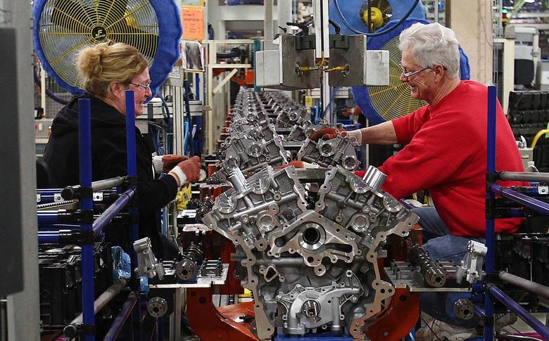 Ford assembly line employees work on 3500 Duramax engine as they move along the assembly line at the Ford Lima Engine Plant in Lima, Ohio, March 28, 2014. REUTERS/Aaron Josefczyk