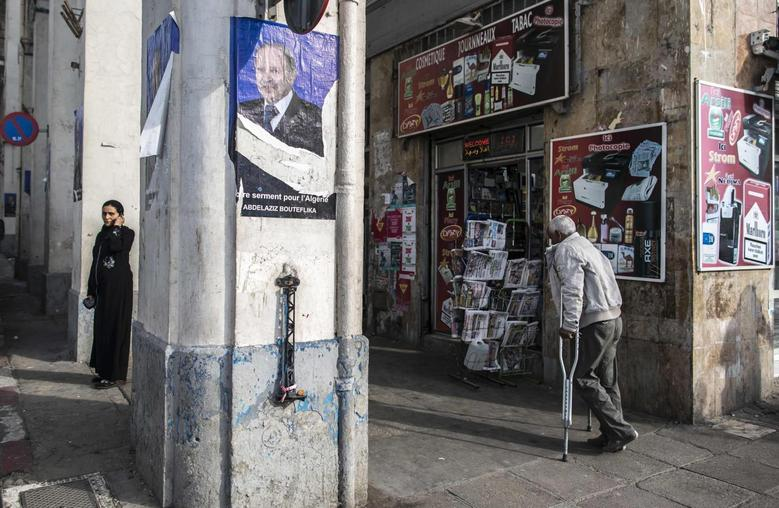 A man walks past an election campaign poster of Algerian president and presidential candidate Abdelaziz Bouteflika at Bab El Oued district in Algiers April 14, 2014. REUTERS/Zohra Bensemra