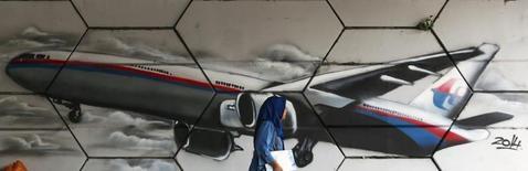 Grafiti do avião desaparecido da Malaysia Airlines, em Kuala Lumpur. A busca por um avião da Malaysia Airlines no fundo do oceano índico foi novamente encurtada nesta quarta-feira, quando problemas técnicos obrigaram um submarino teleguiado dos EUA a voltar à superfície sem ter descoberto nada, segundo autoridades. 15/04/2014. REUTERS/Samsul Said