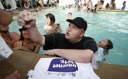 Imagen de archivo del empresario de internet KIm Dotcom firmando camisetas para sus admiradores en un evento en la mansión Dotcom en Coatesville, Nueva Zelanda, abr 13 2014. El magnate de internet Kim Dotcom se baña en la piscina de una mansión de Nueva Zelanda, saluda chocando el puño y charla con los 700 invitados reunidos para celebrar el partido político que lanzó el mes pasado para promover la libertad en la web. REUTERS/Nigel Marple/Files