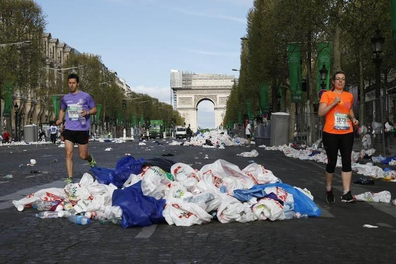 Competitors in the 38th Paris Marathon make their way past discarded plastic bags, used by runners to keep warm befor the start of the race, as they run down the Champs Elysees below the Arc de Triomphe after the start of the footrace in Paris April 6, 2014. REUTERS/Gonzalo Fuentes