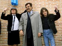 Angus (L) and Malcolm (R) Young, founder members of Australian heavy metal band AC/DC, flank Jose Luis Perez, mayor of the Madrid district of Leganes, following the inauguration of a new street with the group's name in this file photo taken March 22, 2000. REUTERS/Staff/Files
