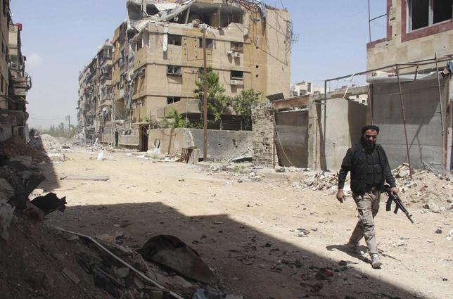 A rebel fighter carries his weapon as he walks along a damaged street in the Mleha suburb of Damascus April 16, 2014. REUTERS/Badra Mamet