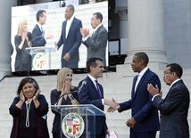 "Los Angeles Mayor Eric Garcetti (C) shakes hands with rapper Jay Z (2nd R) during a news conference after they announced that the ""Made in America"" two-day music festival will be held at Grand Park in front of City Hall over the Labor Day weekend in Los Angeles April 16, 2014. REUTERS/Kevork Djansezian"