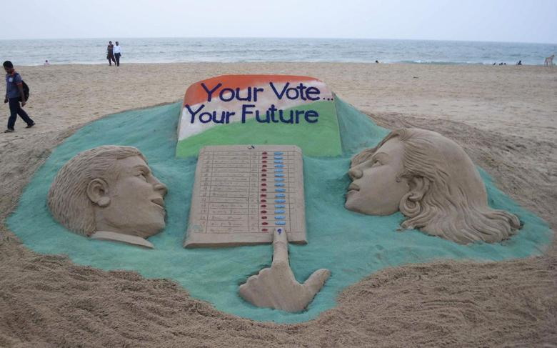 A visitor walks next to a sand sculpture on elections made by Indian sand artist Sudarshan Pattnaik at a beach at Puri in the eastern Indian state of Odisha April 16, 2014. REUTERS/Stringer