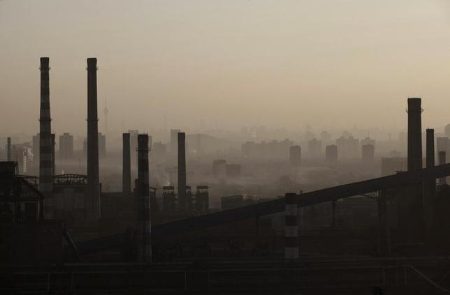 Chimneys and cooling towers of a steel plant are seen through the fog in Beijing, January 17, 2013. REUTERS/Suzie Wong