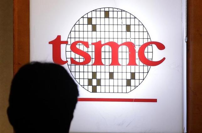 A man sits in front of the logo of Taiwan Semiconductor Manufacturing Co Ltd (TSMC) during an investors' conference in Taipei April 18, 2013. REUTERS/Pichi Chuang