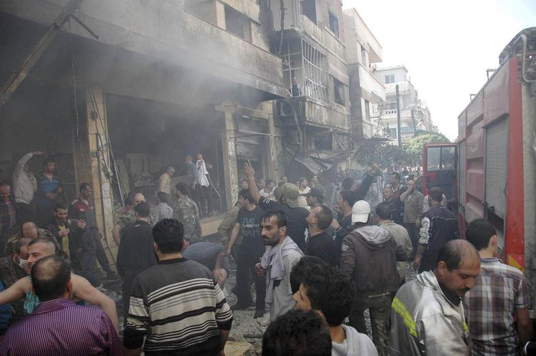 People gather around wreckage after two car bombs at Karm al-Louz neighborhood in Homs city, April 9, 2014, in this handout released by Syria's national news agency SANA. REUTERS/SANA/Handout via Reuters