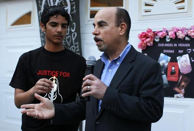 Kassim Alhimidi (R) speaks next to his son Mohammed Alhimidi (L) during a candlelight vigil to remember his wife Shaima Alawadi outside their home in El Cajon, California March 28, 2012. REUTERS/Mike Blake