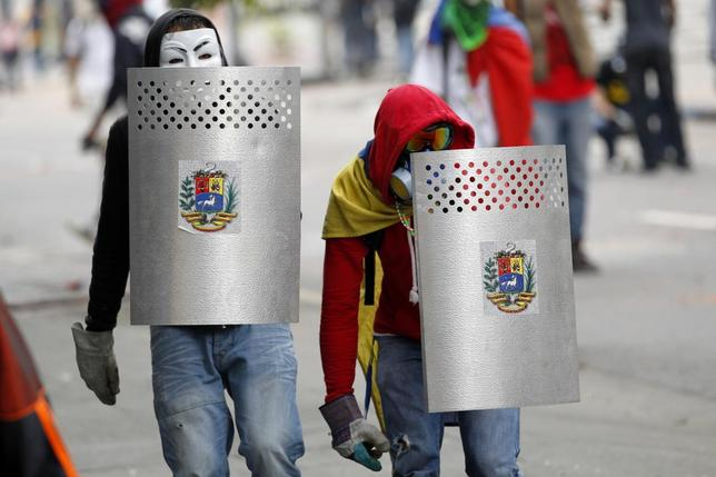 Anti-government protesters cover themselves with shields during riots in Caracas April 17, 2014. REUTERS/Christian Veron