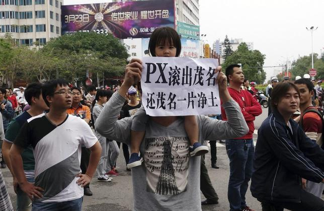 A man and a girl on his shoulders hold up a paper that reads, ''PX (paraxylene petrochemicals) get out of Maoming, return us clean land'', as demonstrators gather to protest against a chemical plant project, near the city government building in Maoming, Guangdong province in this April 3, 2014 file photo. REUTERS/Stringer/Files