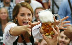 A visitor reaches for of the one of the first mugs of beer after the tapping of the first barrel during the opening ceremony for the 180th Munich Oktoberfest in this September 21, 2013 file photo. REUTERS/Michael Dalder/Files