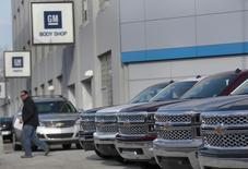A man walks past a row of General Motors vehicles at a Chevrolet dealership on Woodward Avenue in Detroit, Michigan April 1, 2014. REUTERS/Rebecca Cook