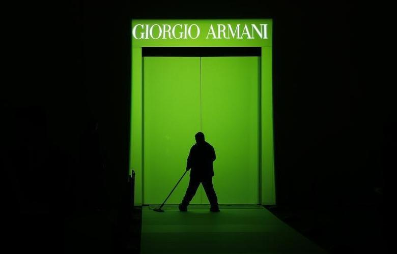 A worker cleans the catwalk before to start Giorgio Armani Autumn/Winter 2014 collection during Milan Fashion Week February 24, 2014. REUTERS/Alessandro Bianchi