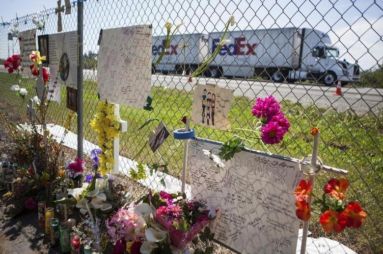 A FedEx truck drives past a makeshift memorial, set up in memory of those who died last week when a FedEx truck collided with a tour bus, beside Interstate 5 in Orland, California, April 17, 2014. REUTERS/Max Whittaker