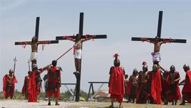 Penitents hang on wooden crosses during the re-enactment of the crucifixion of Jesus Christ on Good Friday in San Fernando, Pampanga in northern Philippines April 18, 2014. REUTERS/Erik De Castro