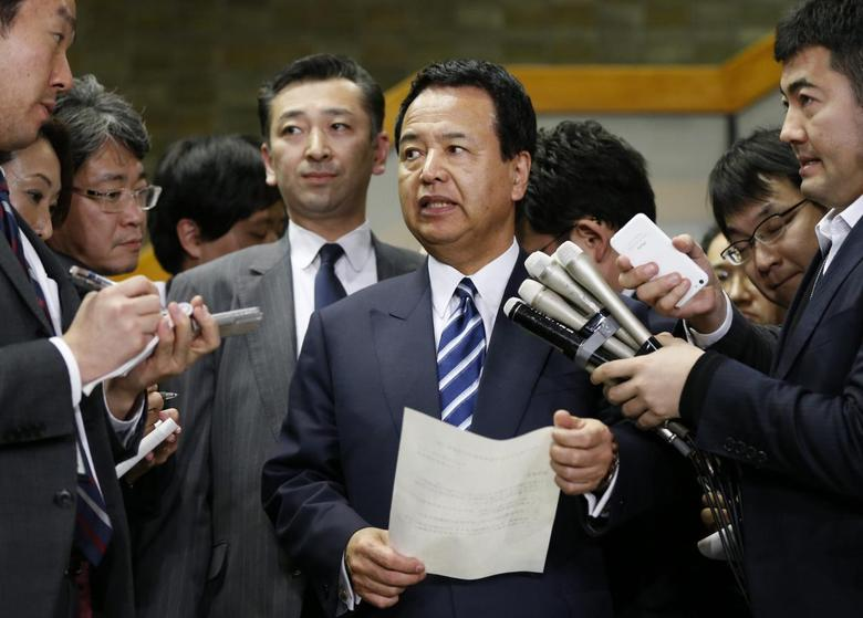 Japan's Economics Minister Akira Amari (C) speaks as he is surrounded by media after meetings with U.S. Trade Representative Michael Froman (not in picture) in Tokyo April 10, 2014. REUTERS/Issei Kato