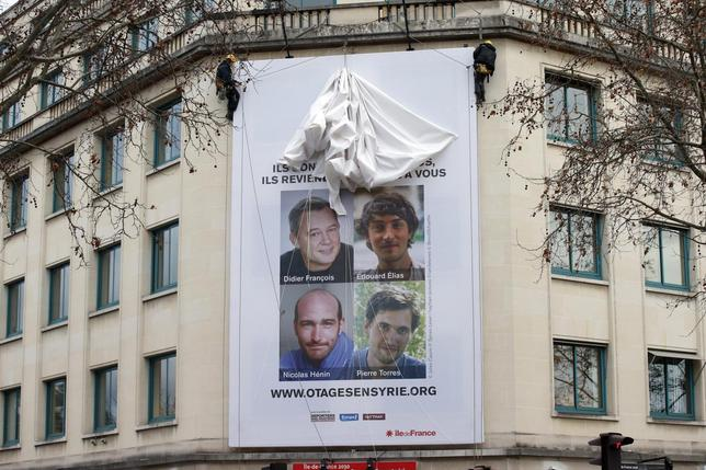 A poster calling for the release of French journalists Didier Francois, Edouard Elias, Nicolas Henin and Pierre Torres is installed on the facade of the Ile de france regional council headquarters in Paris January 6, 2014. REUTERS/Benoit Tessier