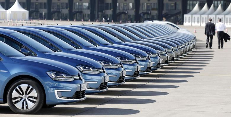 People walk past a row of Volkswagen e-Golf cars during the company's annual news conference in Berlin March 13, 2014. REUTERS/Tobias Schwarz