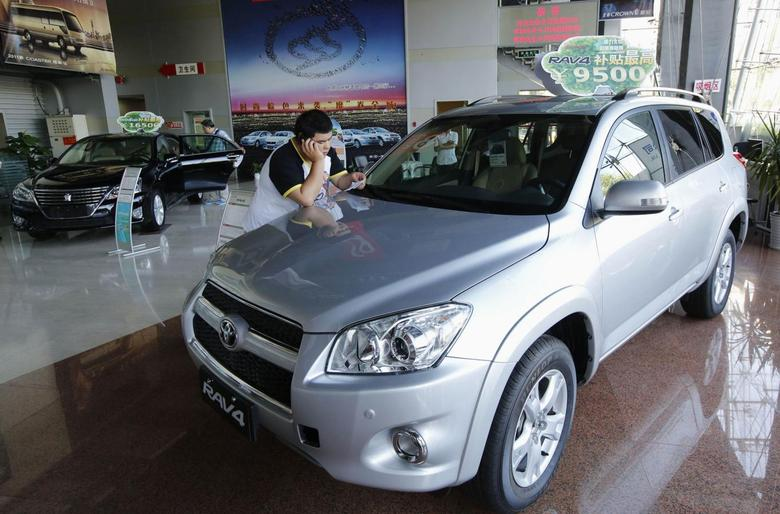 A man uses a mobile phone at a showroom of Toyota Motor in Beijing July 2, 2013. REUTERS/Kim Kyung-Hoon