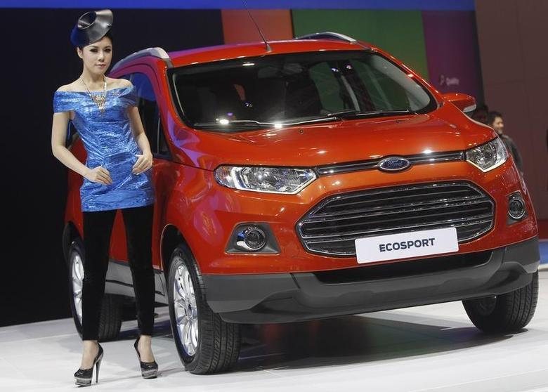 A model poses beside a Ford Ecosport during a media presentation of the 34th Bangkok International Motor Show in Bangkok March 26, 2013. REUTERS/Chaiwat Subprasom