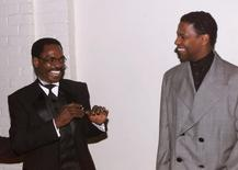 "Actor Denzel Wahington (R), star of the new film ""The Hurricane,"" based on the true story of Rubin ""Hurricane"" Carter (C), an innocent man who fought for 20 years for justice, pose at the film's premiere December 14 in Los Angeles. Washington portrays Carter in the film. FSP/hb - RTRTCC4"