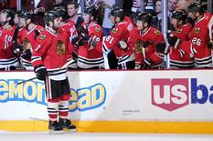 Jan 12, 2014; Chicago, IL, USA; Chicago Blackhawks defenseman Brent Seabrook (7) is congratulated by his teammates for scoring a goal against the Edmonton Oilers during the third period at the United Center. The Blackhawks beat the Oilers 5-3. Mandatory Credit: Rob Grabowski-USA TODAY Sports - RTX17BO4