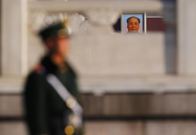 A paramilitary policeman stands guard near a portrait of China's late leader Mao Zedong, at the Tiananmen Square, near the Great Hall of the People, the venue for the closing ceremony of the Chinese National People's Congress (NPC) , in Beijing, March 13, 2014. REUTERS/Petar Kujundzic